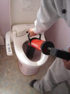 高圧ポンプでトイレのつまりを取り除いている