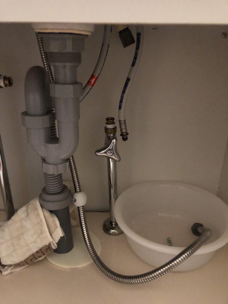 洗面台の下で水が漏れている